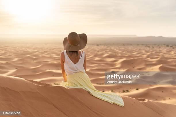lever du soleil dans le désert de merzouga (sahara). une jeune femme caucasienne dans une longue jupe jaune, chemise blanche et chapeau de paille se trouve sur le dessus d'une dune de sable et regarde vers le lever du soleil. - femme marocaine photos et images de collection