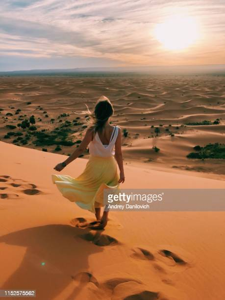 lever du soleil dans le désert de merzouga (sahara). une jeune femme caucasienne se tenant au-dessus d'une dune de sable et regarde vers le lever du soleil. - femme marocaine photos et images de collection
