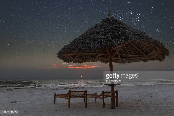 Sunrise in tropical beach of Zanzibar with starry sky