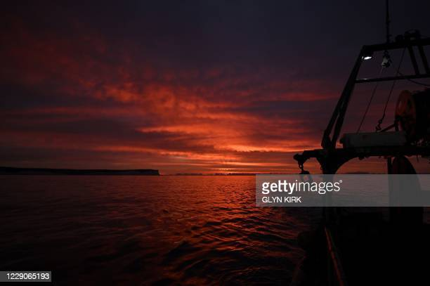 Sunrise is pictured on the horizon as Newhaven Fishing boat skipper Neil Whitney prepares his boat for the first trawl of the day, off the south-east...