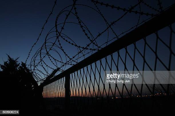 A sunrise is seen through a barbedwire fence at the Imjingak near the Demilitarized zone separating South and North Korea on January 8 2016 in Paju...