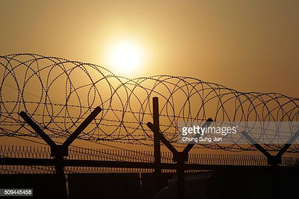 A sunrise is seen through a barbedwire fence at the military check point near the Demilitarized zone separating South and North Korea on February 11...