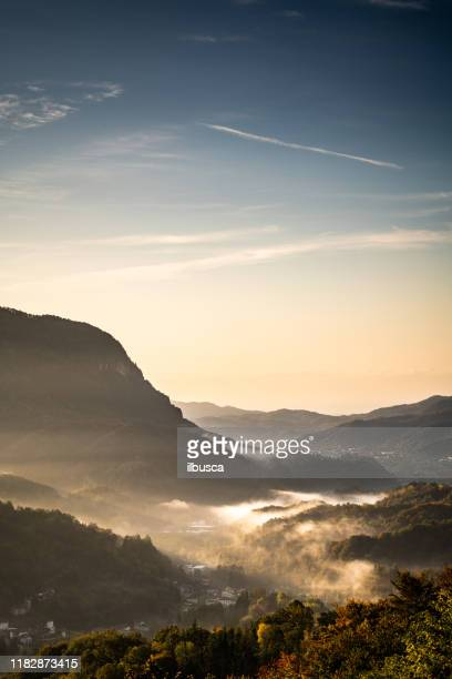 sunrise morning mist in small village on the italian alps, piedmont, monte fenera - valley stock pictures, royalty-free photos & images