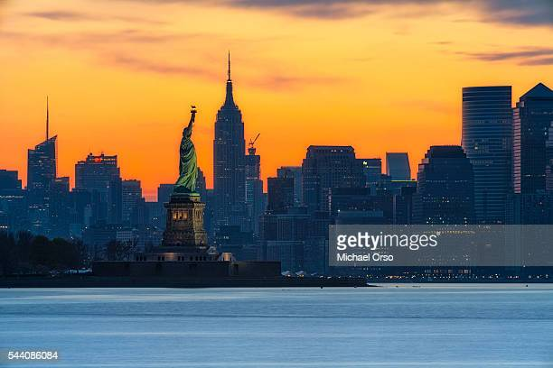 Sunrise NYC, Statue of Liberty and the Empire State Building with lower Manhattan skyline.