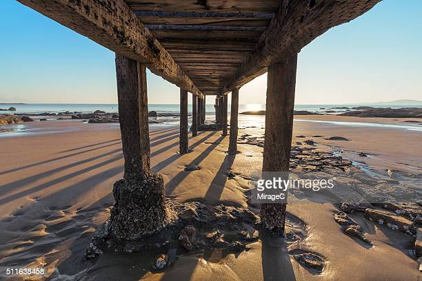 Sunrise on Beach under a Wooden Pier
