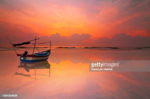 sunrise on beach with reflection of sky and fisherman boat - paesaggio marino foto e immagini stock