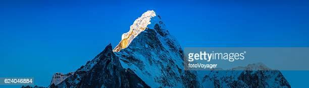 Sunrise on dramatic snow capped mountain peak Ama Dablam Himalayas