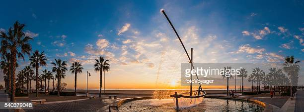 Sunrise on Mediterranean Ocean beach promenade palm trees Valencia Spain