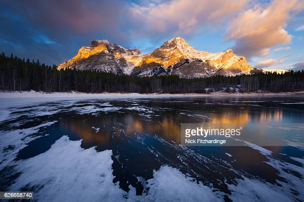 sunrise on mt kidd from a frozen wedge pond, spray valley provincial park, alberta, canada - kananaskis country stock pictures, royalty-free photos & images