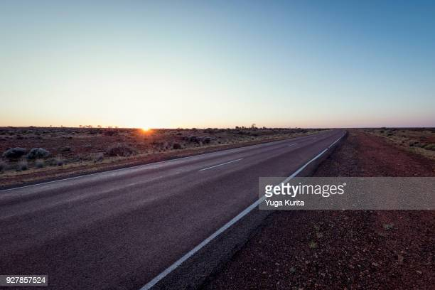 sunrise on the horizon over the country road in the outback - two lane highway stock pictures, royalty-free photos & images