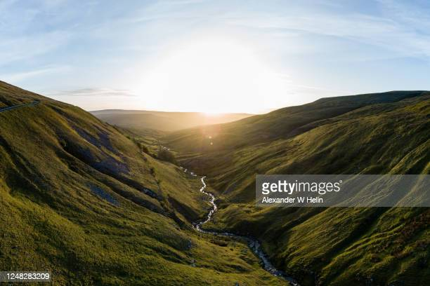 sunrise over a valley - hill stock pictures, royalty-free photos & images
