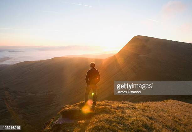 sunrise over a walker on the ridge to cribyn, admiring the view in the brecon beacons national park. - ウェールズ文化 ストックフォトと画像