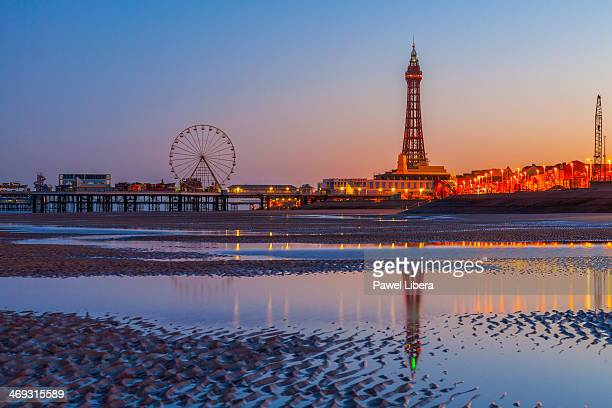 Sunrise over Blackpool Beach at low tide with Blackpool Tower and Big Wheel on Central Pier in the background