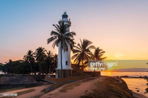 sunrise over galle dutch fort lighthouse surrounded by coconut trees in sri lanka - sri lanka stock pictures, royalty-free photos & images