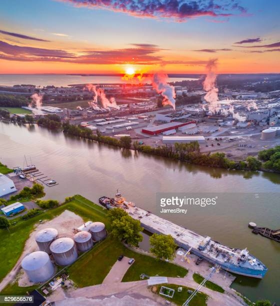 sunrise over industrial riverfront, with ship and factories, aerial view. - green bay wisconsin imagens e fotografias de stock