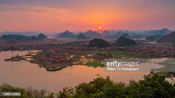 sunrise over lakes and hills of puzhehei - formación karst fotografías e imágenes de stock
