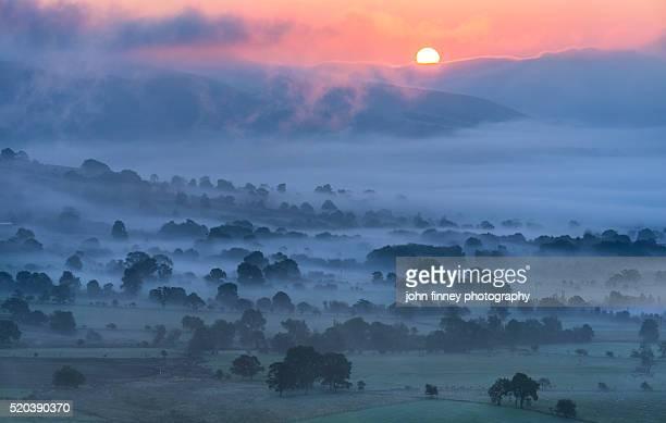 Sunrise over misty valley, English Peak District.