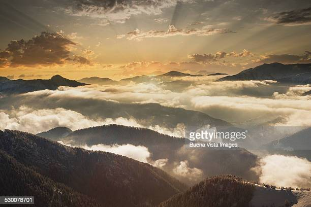 Sunrise over mountains in the clouds in winter
