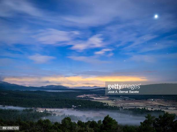 Sunrise over on a valley with mountains, forests of pines, fields and fogs; the moon and the stars still are visible in the sky. Natural park of the Sierra Mariola, Valencia, Spain.
