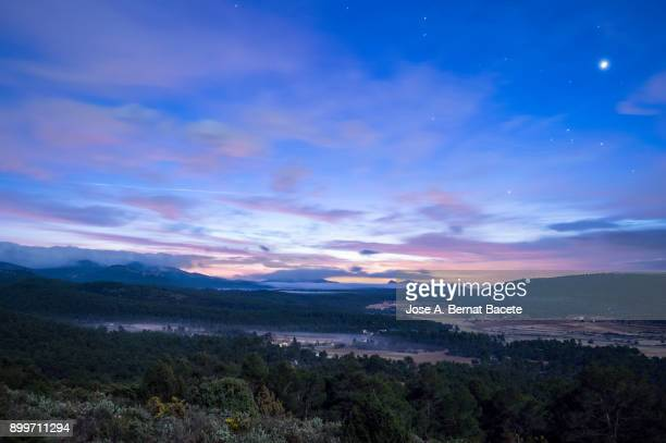sunrise over on a valley with mountains, forests of pines, fields and fogs; the moon and the stars still are visible in the sky. natural park of the sierra mariola, valencia, spain. - twilight stock pictures, royalty-free photos & images
