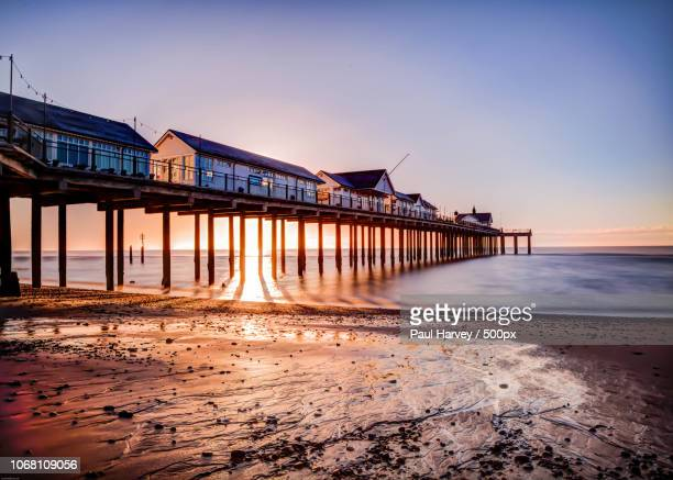 sunrise over pier - east anglia stock pictures, royalty-free photos & images