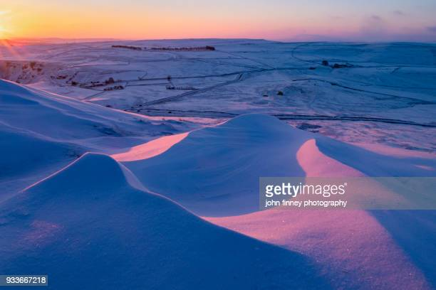 Sunrise over snow drifts in the English Peak District. UK.