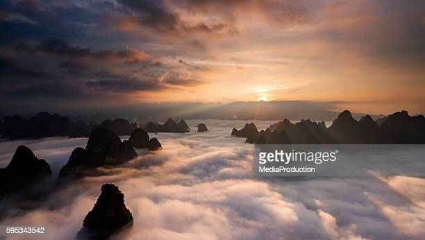 sunrise over the clouds - mountain peak stock pictures, royalty-free photos & images