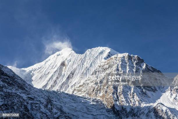 sunrise over the gangapurna peak in the annapurna mountain range in nepal - didier marti stock photos and pictures