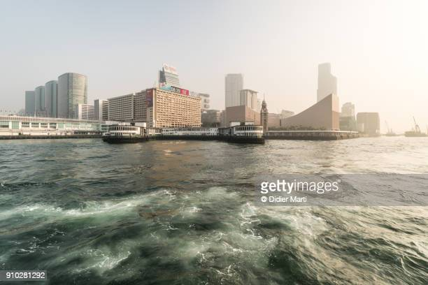 sunrise over the kowloon skyline with the star ferry pier in hong kong - victoria harbour hong kong stockfoto's en -beelden