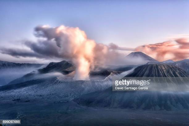 sunrise over the smoking gunung bromo volcano, bromo-tengger-semeru national park, java, indonesia, southeast asia, asia - mt bromo stock photos and pictures