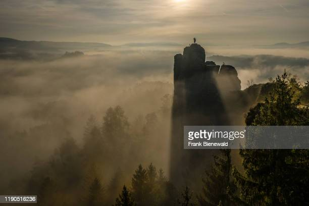 Sunrise over the summit of the rock Mönch in the national Park Saxon Switzerland thick fog is covering the valley of the river Elbe