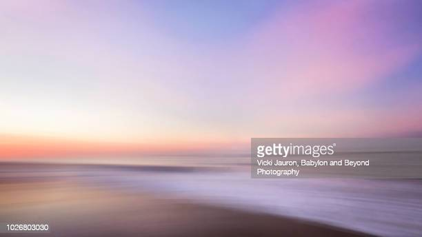 sunrise pastel colors abstract at jones beach in winter, long island, ny - kalmte stockfoto's en -beelden
