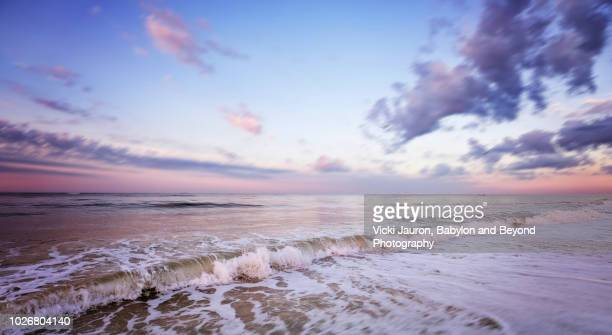 sunrise pastel colors and wave at jones beach in winter, long island, ny - wantagh stock pictures, royalty-free photos & images