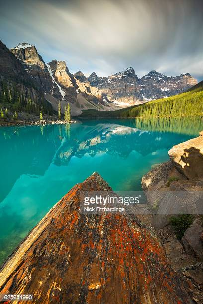 Sunrise reveals the turquoise color of Moraine Lake as well as a photographer's silhouette, Banff National Park, Alberta, Canada