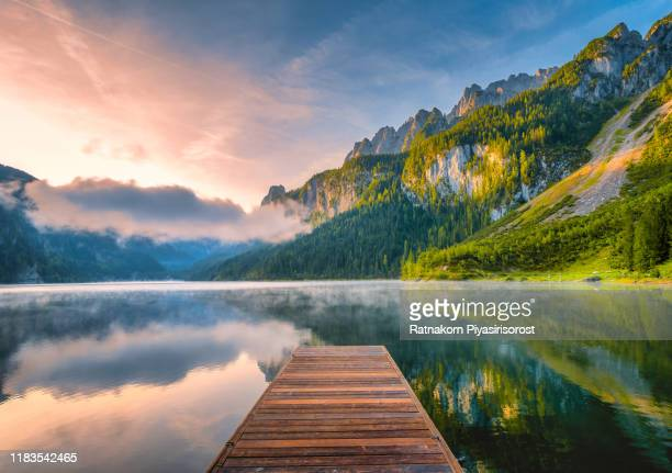 sunrise scene of austrian landscape with forests, fog, meadows, fields and pastures surrounding the lake gosausee with alps mountain - umweltschutz stock-fotos und bilder
