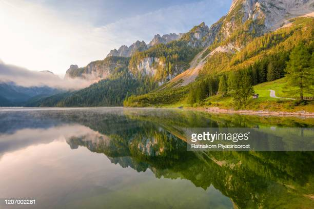 sunrise scene of austrian landscape with forests, fog, meadows, fields and pastures surrounding the lake gosausee with alps mountain - upper austria stock pictures, royalty-free photos & images
