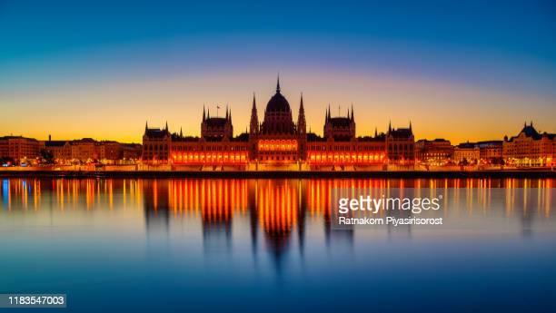 sunrise scene of budapest parliament with dramatic sunrise, budapest, hungary - 対称 ストックフォトと画像