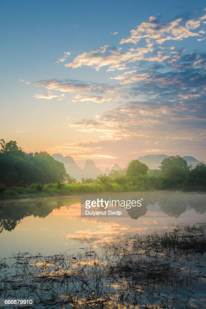 Sunrise scene with mountain and water reflection