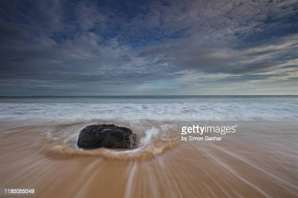 sunrise seascape photograph on beach with water motion over single rock - north sea stock pictures, royalty-free photos & images