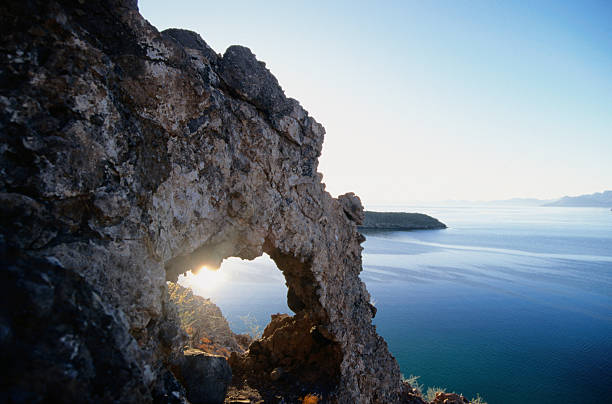Sunrise seen through a naturally formed arch in a cliff at Bahia Concepcion.