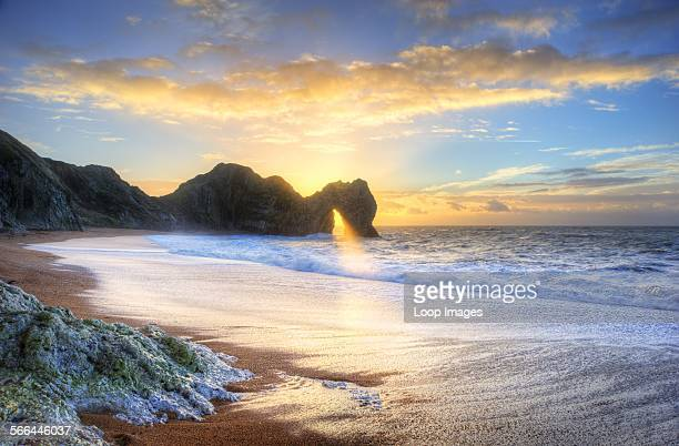 Sunrise shines through the arch of Durdle Door on the Jurassic Coast