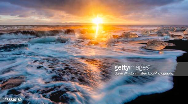 sunrise time exposure with blurred water and reflections aticeland's famous iceberg beach - jökulsárlón lagoon stock pictures, royalty-free photos & images