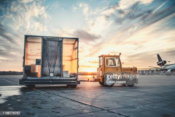 sunrise tug on tarmac at airport - cargo container stock pictures, royalty-free photos & images