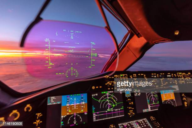 sunrise view from modern aircraft cockpit with heads up display and flight instruments - navigational equipment stock pictures, royalty-free photos & images