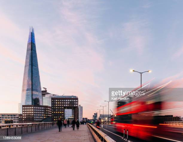 a sunrise view of london bridge with blurred traffic and passer's by - greater london stock pictures, royalty-free photos & images