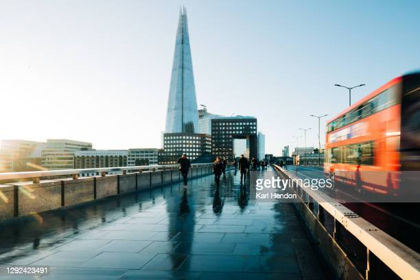 a sunrise view of london bridge with blurred traffic and passer's by - central london stock pictures, royalty-free photos & images