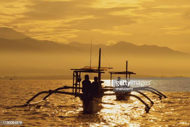 sunrise view over tourists waiting for wild dolphin at lovina beach in bali, indonesia. - shaifulzamri stock pictures, royalty-free photos & images