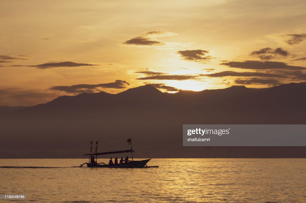 Sunrise view over tourists waiting for wild dolphin at Lovina beach in Bali, Indonesia. : Stock Photo