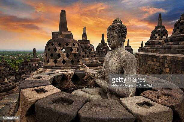 Sunrise with a Buddha Statue with the Hand Position of Dharmachakra Mudra in Borobudur, Magelang, Central Java, Indonesia