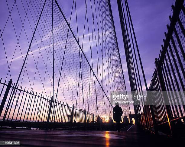 Sunrise with commuter walking on Brooklyn Bridge